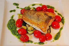Auf der Haut gebratenes Fischfilet auf gegrilltem Zucchinigemüse mit Bärlauchpesto und marinierten Tomaten