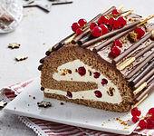 Weihnachtliche Schokoladen-Biskuitrolle mit Spekulatius und roten Johannisbeeren